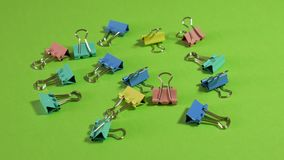 Colorful Binder clips on green background. Colorful Binder clips rotating on green background stock video