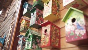 Colorful bird houses. Handmade wooden birdhouse on log house. Birdhouses on the wall. Neighborhood. Wooden birdhouse in stock video
