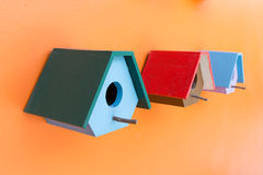 Colorful bird nest wood box decorated on orange wall Royalty Free Stock Image
