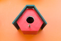 Colorful bird nest wood box decorated on orange wall Stock Image