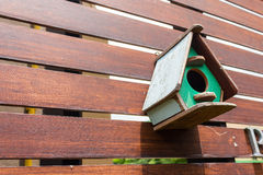 Colorful birdhouse on wooden fence Stock Images