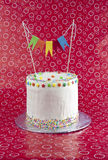 Colorful birthday cake. Birthday cake with rainbow flags on funky red background royalty free stock photo