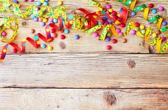 Colorful birthday, carnival or holiday background. With twirled party streamers and sugared candy on a natural rustic wood background with copy space stock photography