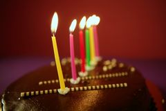 Colorful birthday light candles in chocolate cake Royalty Free Stock Images