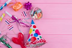Colorful Birthday party supplies on pink wood.