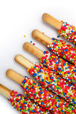 Colorful biscuit stick coated enamel rainbow sugar with white space background. For writing wording Stock Photos
