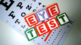 Colorful blocks spelling out eye test falling onto eye test stock footage