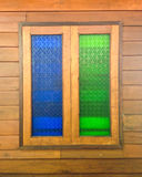 Colorful blue and green glass windows on brown wood wall Stock Image