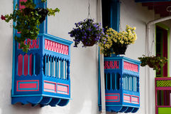 Colorful blue and red house front with flowers on Royalty Free Stock Photo