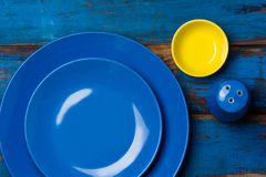 Colorful blue yellow background with empty plates. Napkin, sat shaker on wooden table. Top view, copy space stock image