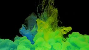 Colorful blue and yellow ink mixing in water, swirling softly underwater on black background with copy space stock video footage
