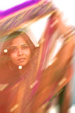 Colorful Blur of Indian Sari. A young, 20 something, Indian woman with long black hair, dressed in traditional Indian sari, is photographed through a purple Stock Photography