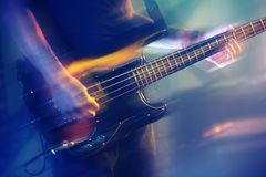 Blurred bass guitar player on a stage. Colorful blurred rock music background, bass guitar player on a stage with colorful illumination Royalty Free Stock Photo