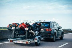 Colorful BMW suv X5 driving fast on French highway with trailer. Nice, France - May 7, 2016: Rear view of Modern BMW SUV X5 driving fast on French highway with stock image
