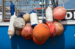 Colorful boat bumpers. Group of colored plastic floats on side of blue boat used as bumpers Stock Photography