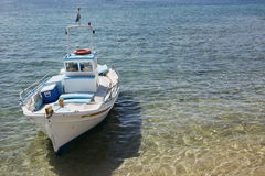 Colorful Boat on Clear Blue Water. Colorful boat docked near the shore in Mykonos, Greece. Water is clear and sand is visible through the water. Focus fades away royalty free stock image