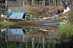 Colorful boat complete with supplies in a pond with reflections. Stock Photos