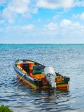A colorful boat floats in shallow water in the caribbean sea stock photo
