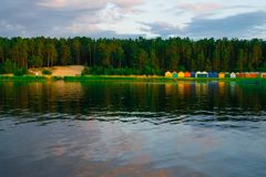 Colorful boat house on the edge of the water. Bright orange and green building is a waterside garage for boats. Colorful boat house on the edge of the water stock image