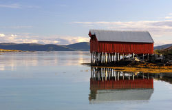 Colorful boat house reflected in the fjord waters Royalty Free Stock Photos
