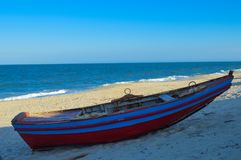 Colorful Boat at Macaneta beach in Maputo Mozambique. Aggressive waves crashing , blue and red color Royalty Free Stock Images