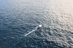 Colorful boat on the sea. Small colorful boat streaks away across the ocean towards the sun Royalty Free Stock Images