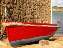 Colorful boat by stone wall beside the sea. Bright red and blue painted boat beside a stone wall by the sea Stock Photos