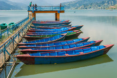 Colorful boats anchored to pier. Stock Photos