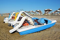 Colorful boats on Eraclea beach, Italy. Series of colorful boats and umbrellas on the beach of Eraclea, in the province of Venice, Italy royalty free stock photography