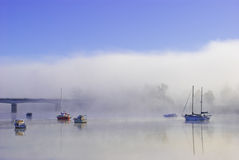 Colorful boats on a foggy river. In a crisp morning Royalty Free Stock Photos