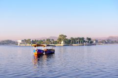 Colorful boats in front of an island on a lake of blue water. Colorful boats stationed on the famous lake fateh sagar in Udaipur floating on the beautiful blue Royalty Free Stock Images