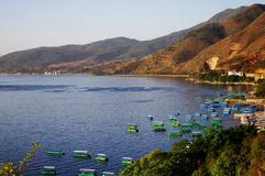 Colorful boats in lake beside mountain. Blue lake Royalty Free Stock Photos