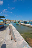 Colorful boats Marsaxlokk. MARSAXLOKK, MALTA - SEPTEMBER 15, 2015: Colorfully painted small wooden boats moored in the clear turquoise water of popular fishing Stock Photography