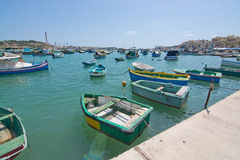 Colorful boats Marsaxlokk. MARSAXLOKK, MALTA - SEPTEMBER 15, 2015: Colorfully painted small wooden boats moored in the clear turquoise water of popular fishing Royalty Free Stock Photos