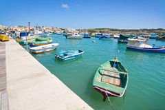 Colorful boats Marsaxlokk. MARSAXLOKK, MALTA - SEPTEMBER 15, 2015: Colorful painted small boats moored in the clear turquoise water on a sunny day on September Royalty Free Stock Photography