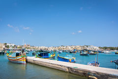 Colorful boats Marsaxlokk. MARSAXLOKK, MALTA - SEPTEMBER 15, 2015: Colorful painted small boats moored in the clear turquoise water on a sunny day on September Royalty Free Stock Image