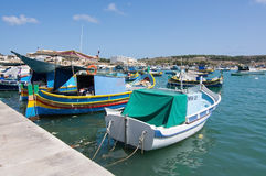 Colorful boats Marsaxlokk. MARSAXLOKK, MALTA - SEPTEMBER 15, 2015: Colorful painted small boats moored in the clear turquoise water on a sunny day on September Stock Images