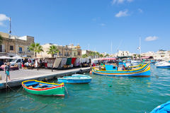 Colorful boats Marsaxlokk. MARSAXLOKK, MALTA - SEPTEMBER 15, 2015: Colorful painted small boats moored in the clear turquoise water on a sunny day on September Royalty Free Stock Photo