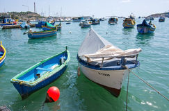 Colorful boats Marsaxlokk. MARSAXLOKK, MALTA - SEPTEMBER 15, 2015: Painted small wooden boats moored in the clear turquoise water on a sunny day on September 15 Royalty Free Stock Images