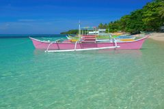 Colorful boats. Moored on the azure clear surface of the island of Siargao, Philippines stock photos