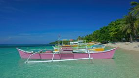 Colorful boats. Moored on the azure clear surface of the island of Siargao, Philippines Stock Images