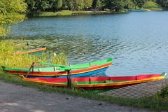 Colorful boats near the shore of the lake and a pontoon on the background of water and forest Stock Image