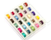 Colorful bobbins. Box of colorful bobbins on white background royalty free stock photography
