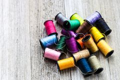 Colorful bobbins with sewing threads piled up on rustic wooden background with copy space royalty free stock photos