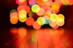 Colorful bokeh background with rustic wood foreground Stock Images