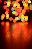 Colorful bokeh background with rustic wood foreground Royalty Free Stock Photos