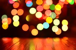 Colorful bokeh background with rustic wood foreground Royalty Free Stock Image