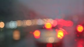 Colorful bokeh with street light at night rain falling on car traffic in the road. A rainy storm at night stock video footage