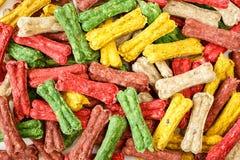 Colorful bone shaped dog treats background. Dog treats background. Colorful bone shaped chews for rewarding dogs royalty free stock photo