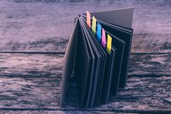 Colorful bookmarks for documents with black diary on wooden back stock photos